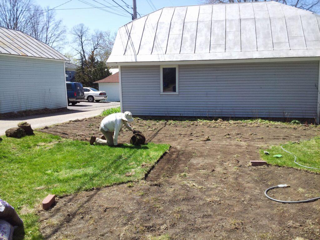Neil rolling up sod in a backyard
