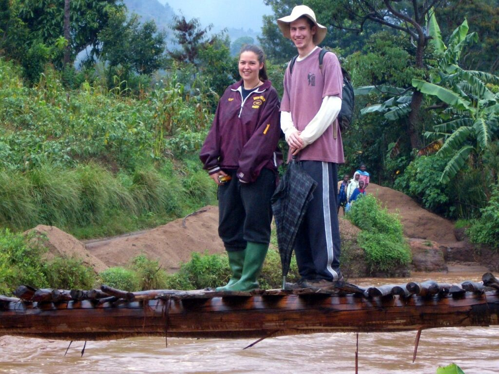 Clare and Neil on a log walking bridge over a river in Tanzania
