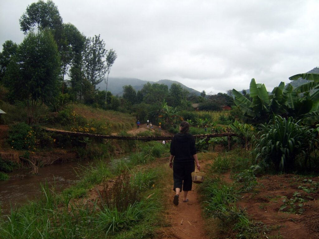 Clare walking on a path through mountain farms in Tanzania